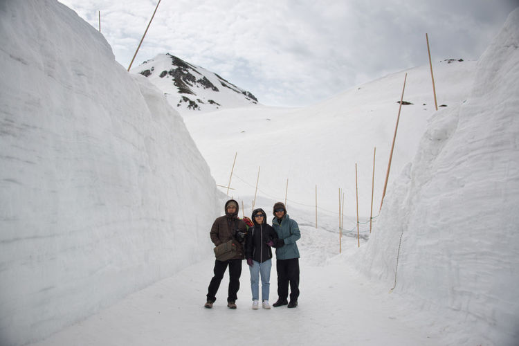 Friends standing on snow covered 0field against sky