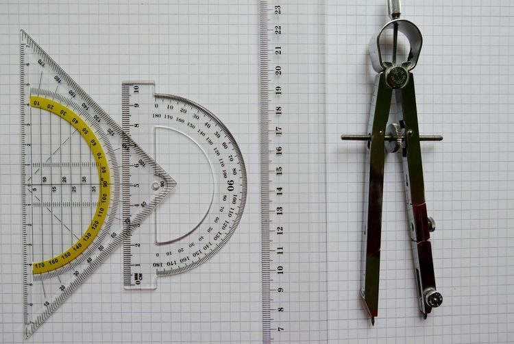 Directly Above Shot Of Set Square And Protractor With Drawing Compass By Ruler On Book