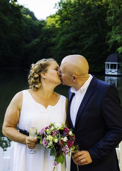Wedding couple kissing against lake