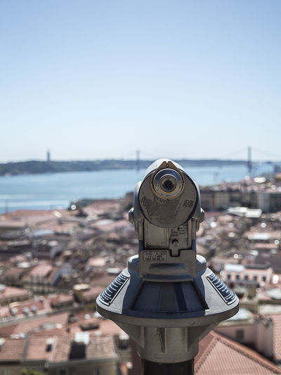Close-up of hand-held telescope against town