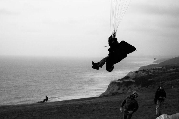 Tourist paragliding at coast