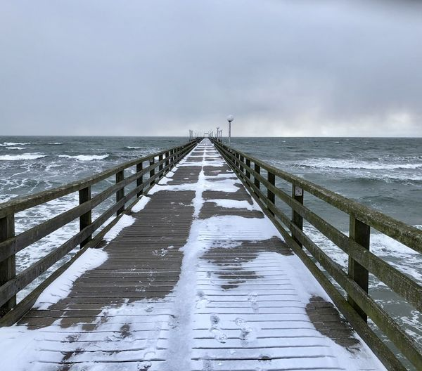 Pier over sea against sky during winter