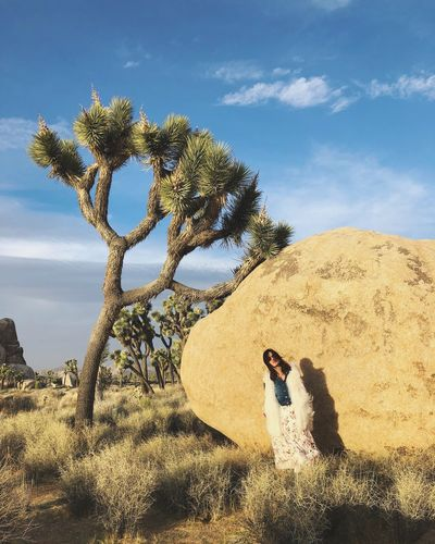 Woman standing by rock formation and trees on field against sky
