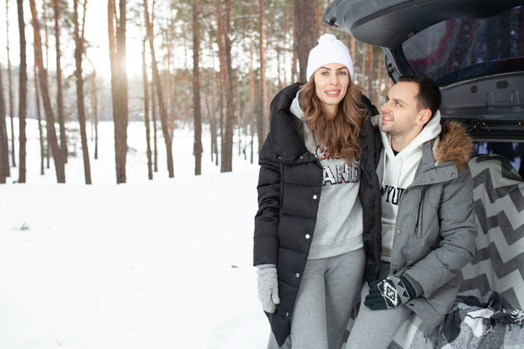 Happy couple by car in forest during winter