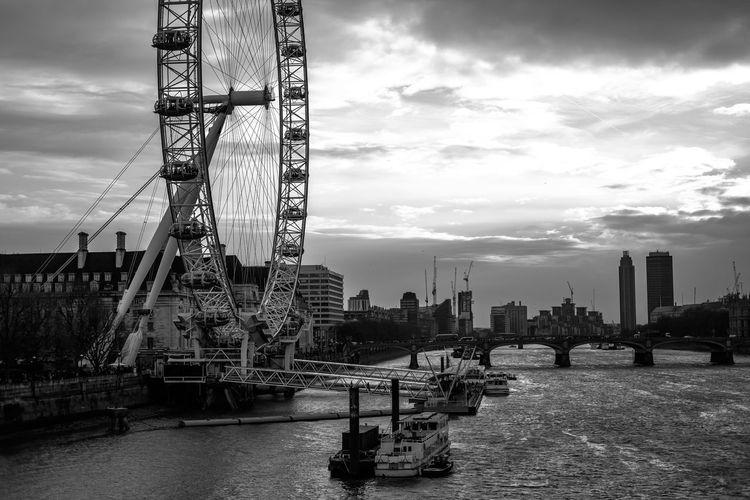 London Eye By Thames River Against Sky