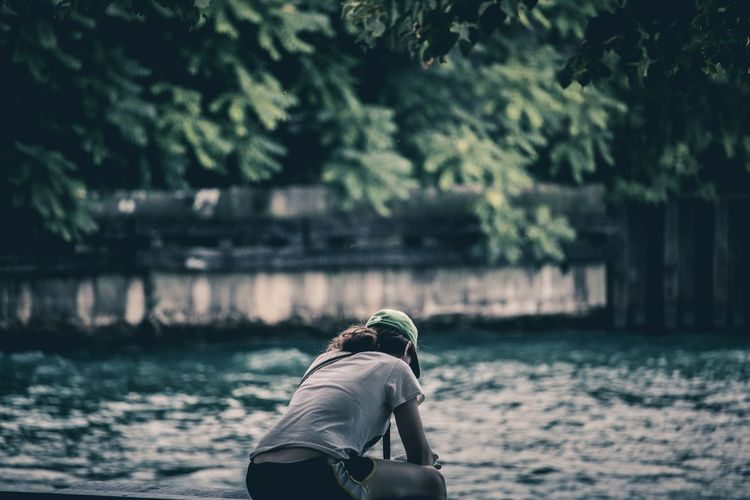 Rear view of girl photographing water