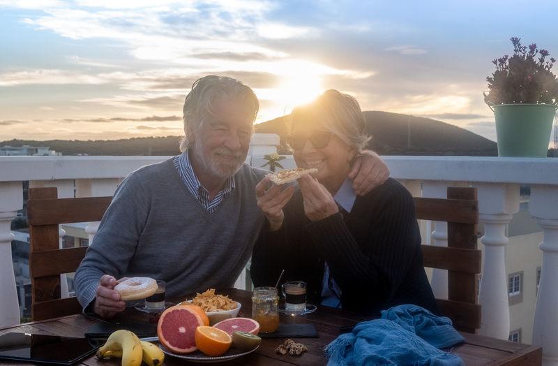 Smiling senior couple enjoying food at sunset