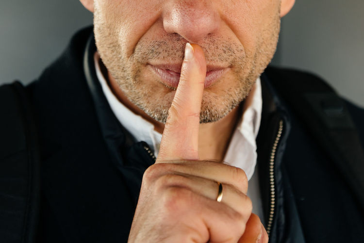 Midsection of man with finger on lips