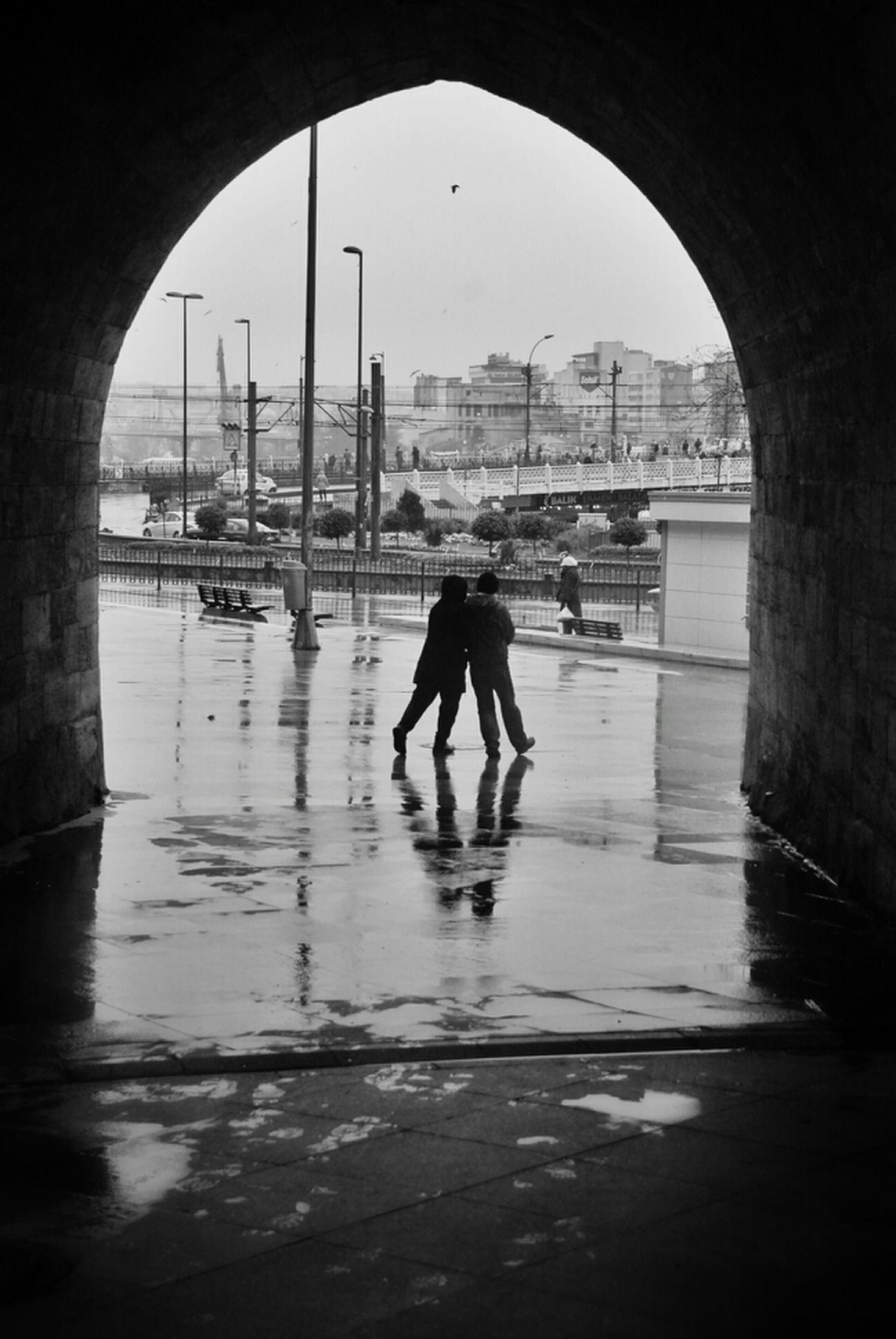 architecture, full length, built structure, walking, building exterior, rear view, men, water, city, lifestyles, arch, street, reflection, person, city life, rain, transportation, wet