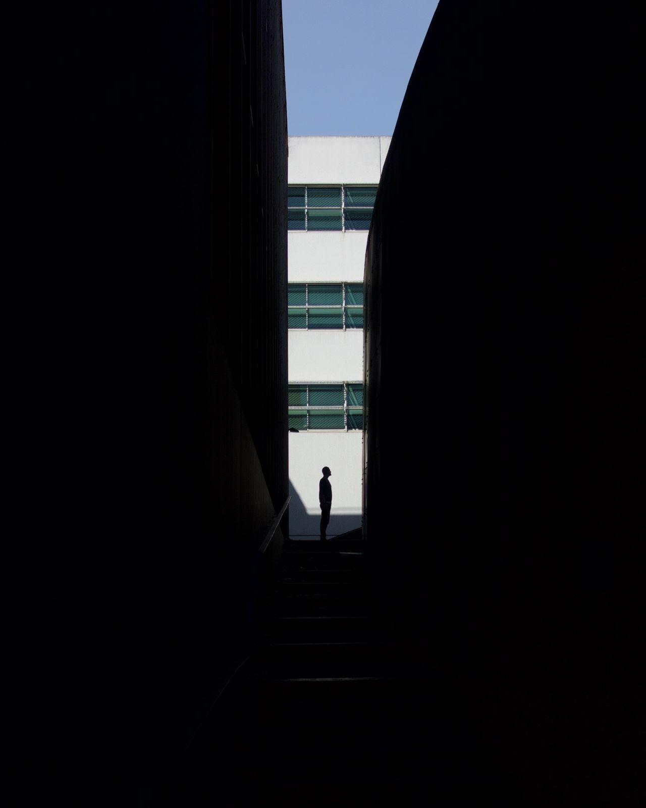 Silhouette man amidst buildings
