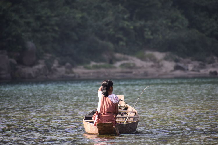Rear view of woman fishing in lake