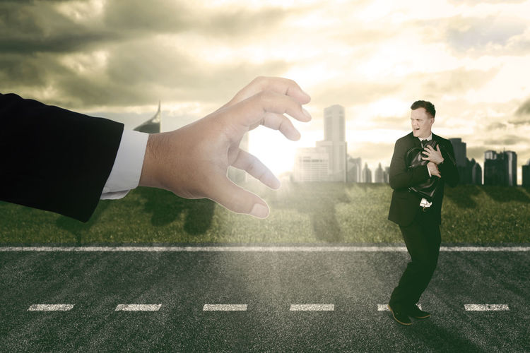 Cropped hand of person holding businessman in city during sunset