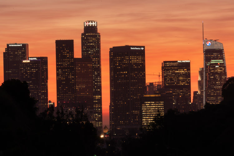 Illuminated buildings in city against sky at sunset