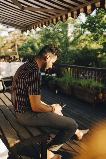 Side view of young man sitting on bench