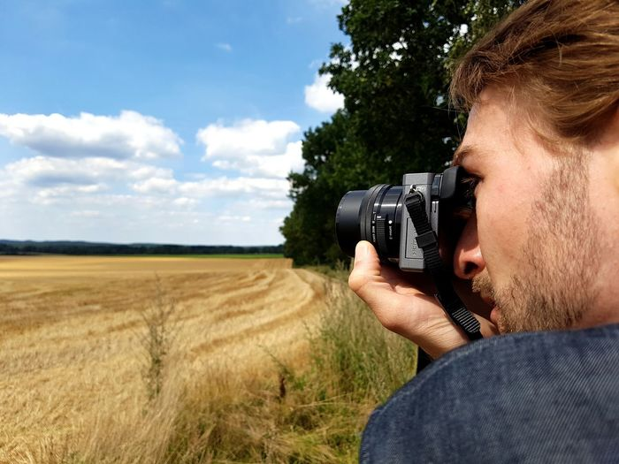 Close-up of young man photographing field through camera