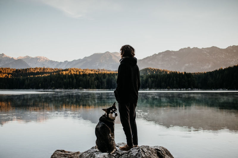 Girl is standing on a rock with her dog at lake Eibsee Berchtesgaden , Germany Eibsee Adventuers Adventure Alps Animal Beauty In Nature Dog Lake Leisure Activity Lifestyles Mammal Mountain Mountain Range Mountains One Person Outdoors Pet Owner Real People Rear View Standing Water