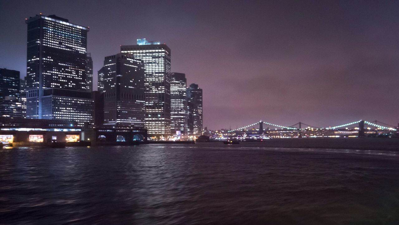River And Illuminated Buildings At Manhattan During Night