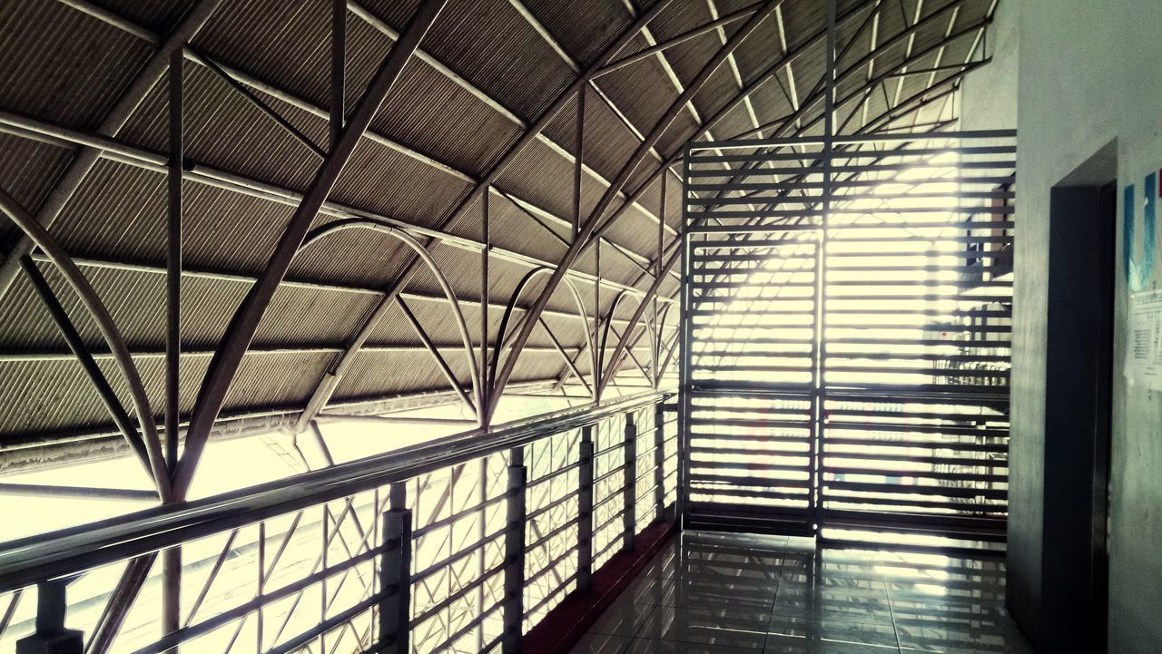 architecture, indoors, built structure, building, pattern, no people, modern, window, glass - material, day, ceiling, low angle view, sunlight, design, architectural feature, transportation, absence, empty, metal, skylight, steel