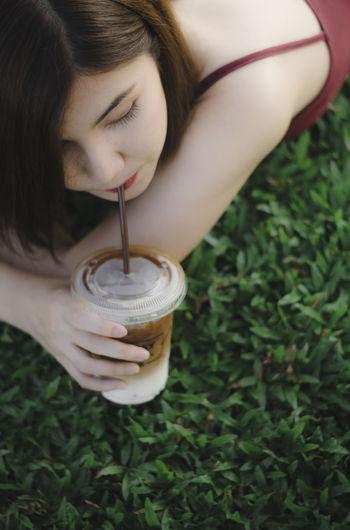 Woman drinking coffee on field