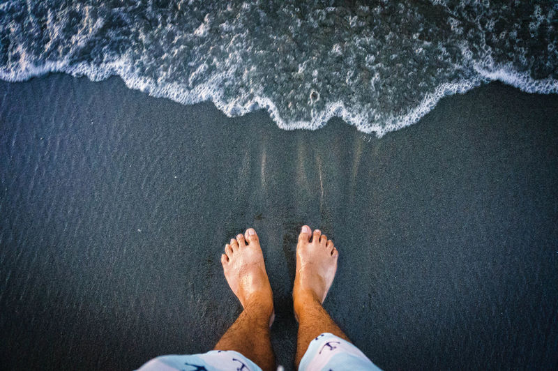 Foot in the black sand EyeEmNewHere Foot Sand Low Section Water Beach Standing Human Leg Sea barefoot Directly Above High Angle View Human Foot Human Feet Toe Sole Of Foot