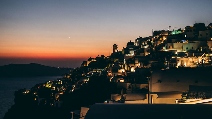 Illuminated townscape by sea against sky during sunset
