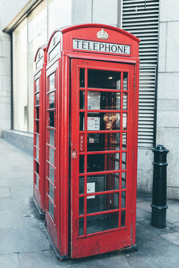 Red telephone booth in city