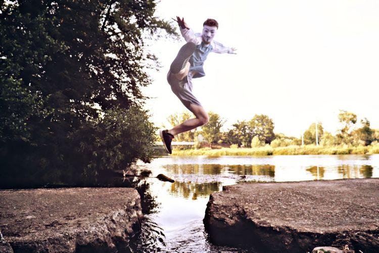 Man jumping in lake against sky