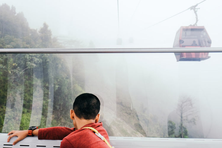 Man sitting by window watching cable car