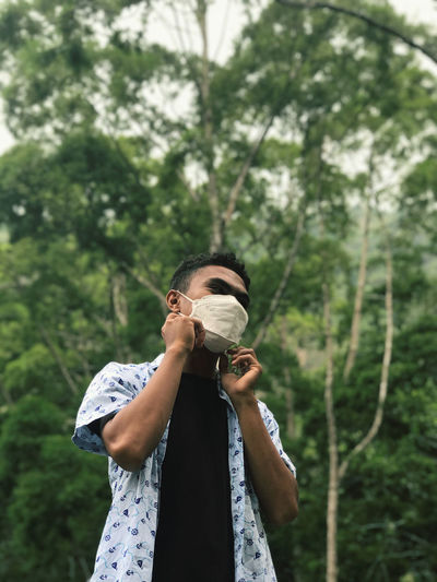 Man wearing protective face mask against trees