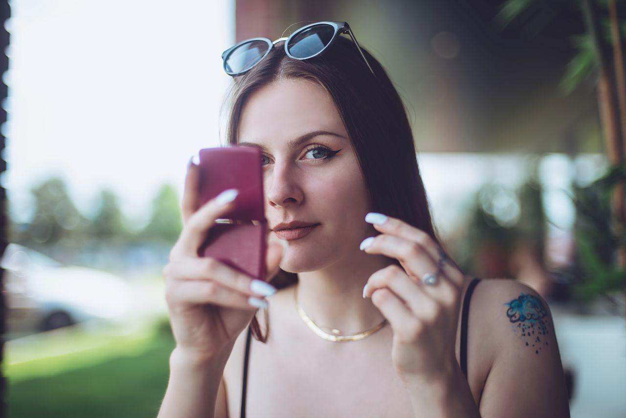 Close-Up Of Young Woman Checking Make-Up