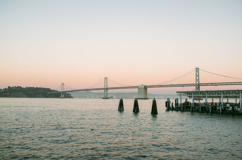 Oakland bay bridge over water against sunset sky