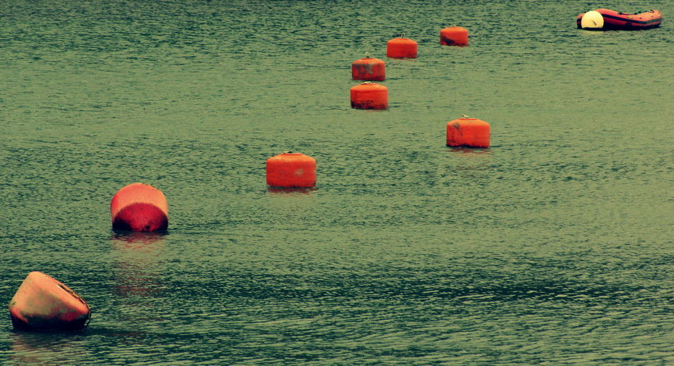 High angle view of buoys floating on water in lake