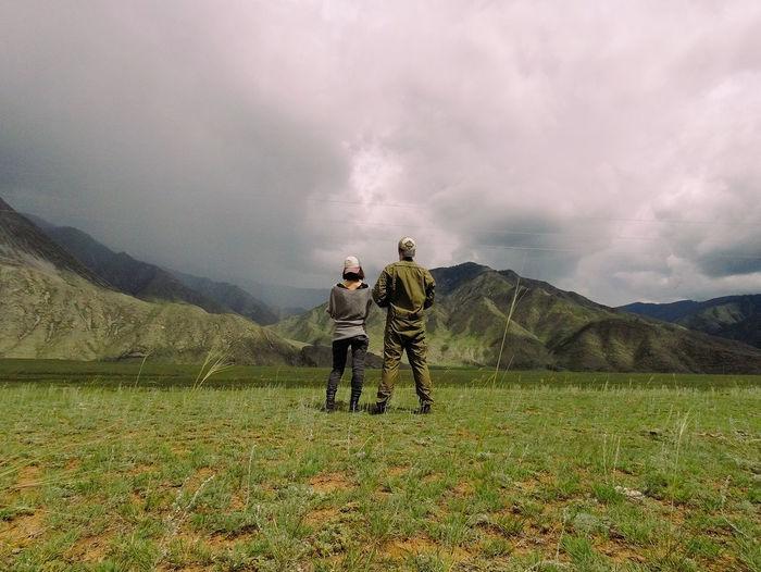 Rear view of men on field against sky