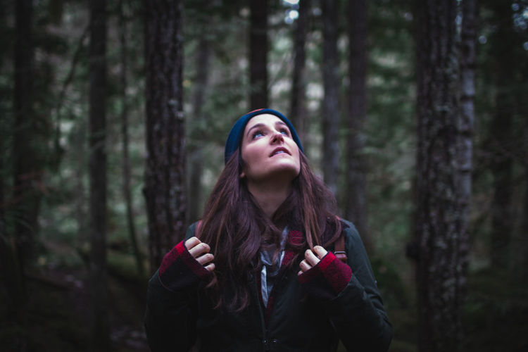 Close-up of young woman looking up in forest