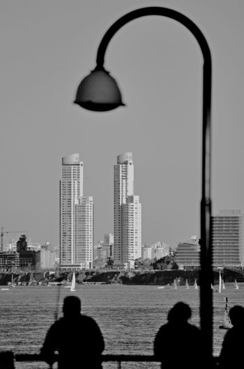 People on sea by buildings against clear sky