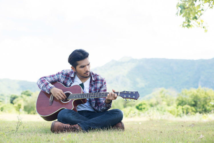 Man playing guitar while sitting on field against sky