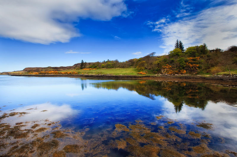 Panoramic view of Loch Dunvegan, Scotland, UK Arrival Blue Day Dunvegan Isle Of Skye Lake Lake View Lakeshore Landscape Lock Natural Parkland Nature No People Outdoors Reflection Reflection Lake Scenics Scotland Scottish Highlands Sky Sunset Travel Destinations Tree Vacations Water