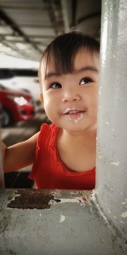 Cute baby girl looking away while standing by pillar