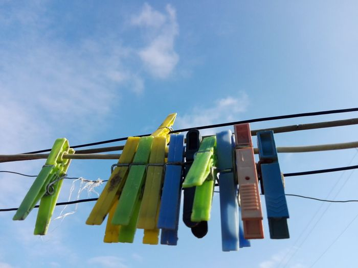Low angle view of clothespin hanging on clothesline