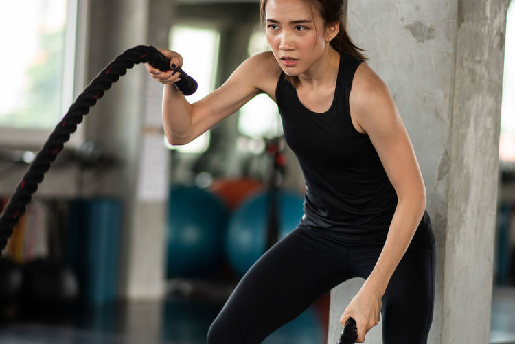 Young Woman Exercising With Rope At Gym