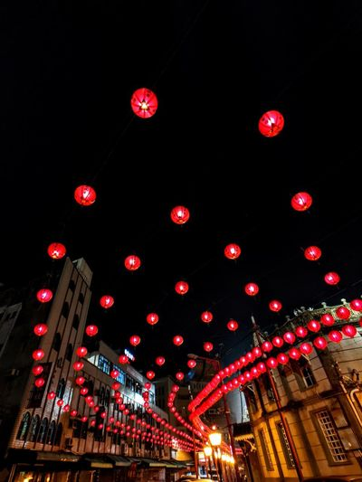 Low angle view of illuminated lanterns hanging amidst buildings in city at night