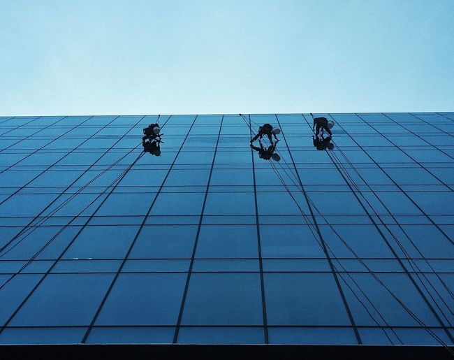 Low angle view of workers cleaning buildings against clear sky