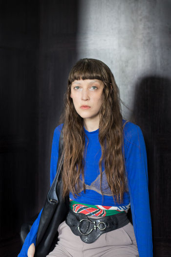Portrait of teenage girl sitting against blue wall