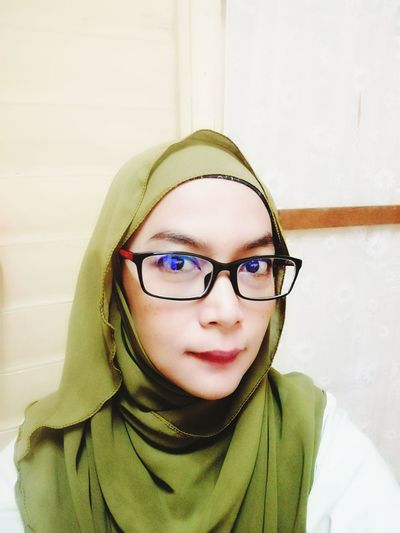 Close-up portrait of woman wearing hijab and eyeglasses