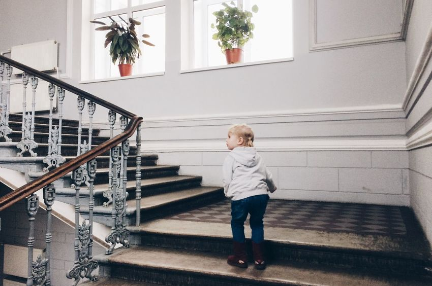 Architecture Blond Hair Built Structure Casual Clothing Childhood Day Full Length Hand Rail Indoors  Lifestyles One Person People Railing Real People Staircase Stairs Standing Steps Steps And Staircases