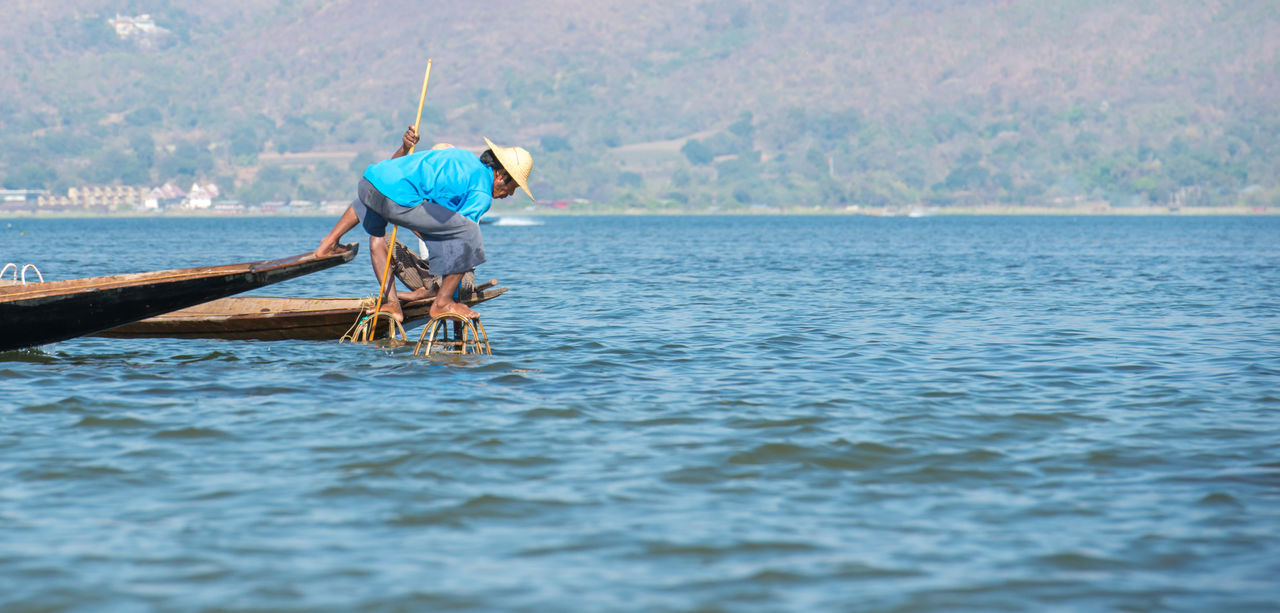 water, nautical vessel, sea, transportation, boat, real people, oar, mode of transport, one person, nature, outdoors, sailing, full length, waterfront, day, fisherman, wooden raft, standing, scenics, occupation, beauty in nature, men, rowing, outrigger, sky, people