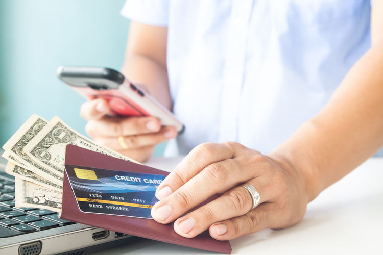 Online payment, Man's hands holding a credit card, passport and money. Using mobile phone for booking hotel and flight Hotel Trip Passport Cart Traveler Plastic Cards Concept Entering E-commerce Cvv Ordering Wireless Tax Male Order Debit Smart Security Man Typing RISK Information Data Lifestyle Phone Ecommerce Keyboard Notebook Finance Electronic Internet Store Home Buy Technology Commerce Banking Using Purchase Business Pay Computer Shopping Laptop Holding Payment Online  Card Credit