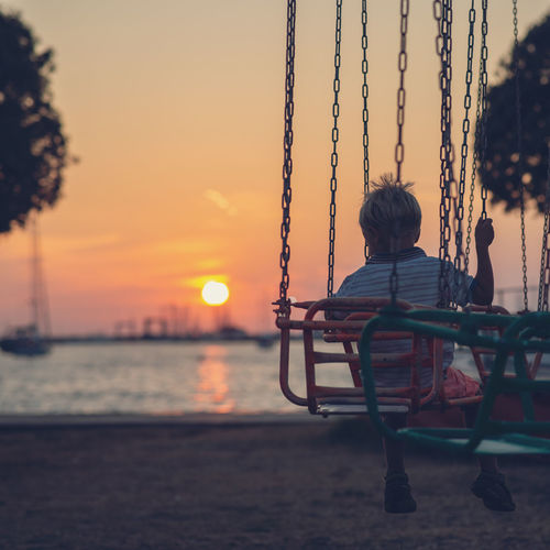 Rear view of boy sitting on swing at beach against sky during sunset