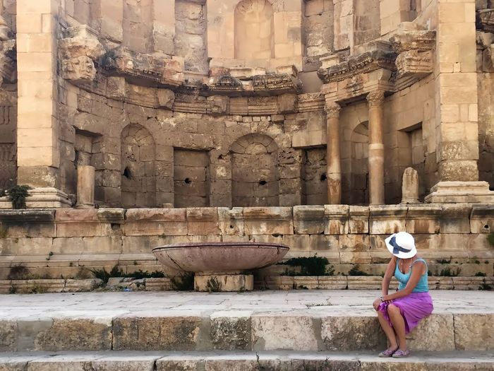 Woman sitting on steps by nymphaeum