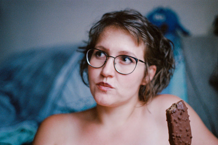 Close-up portrait of woman on bed at home eating ice cream